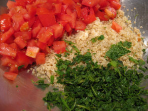 The start of making tabouli - the chopped tomato, cooked quinoa and chopped mint.